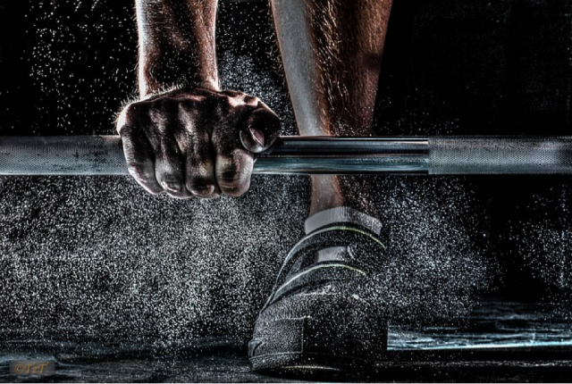 Man lifting weight with sweat flying in air.