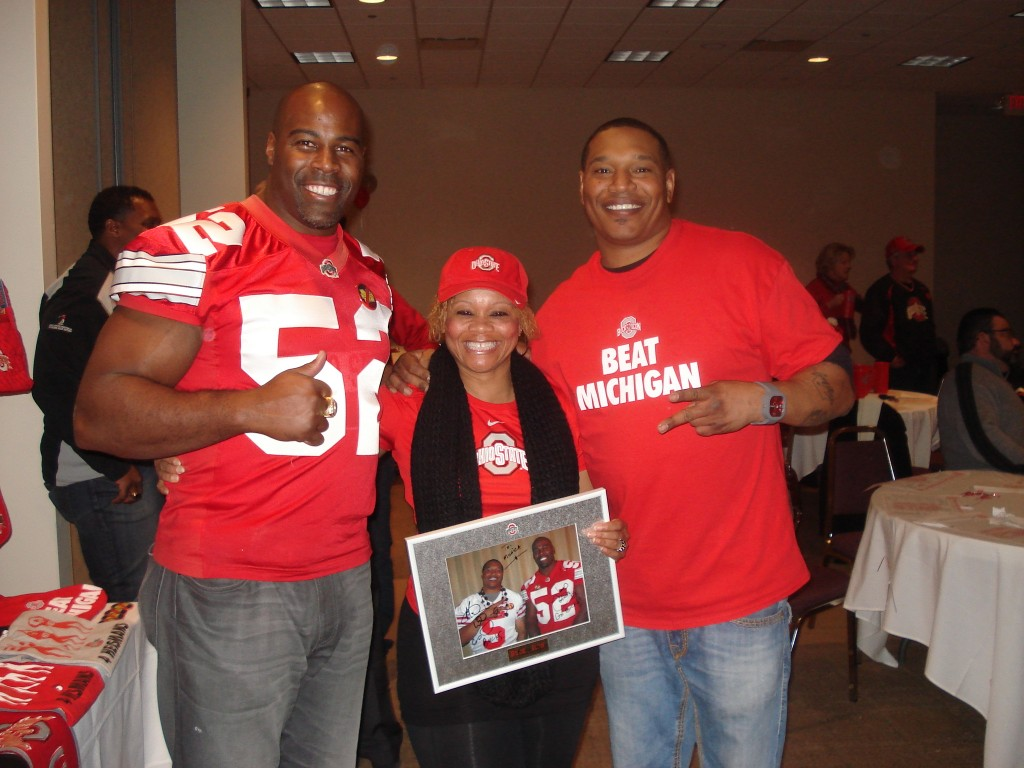 Monica Homer, center, holds a signed photo from football alumni James Cotton and Courtland Bullard she received at Buckeye Bash 2014.