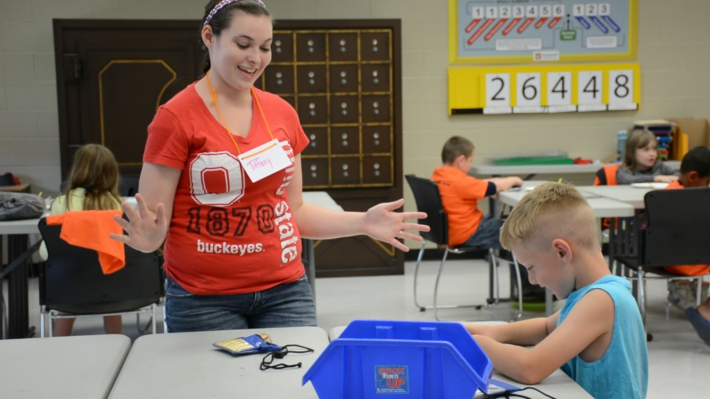 Stephanie Tilley, an Early Childhood Education major at The Ohio State University at Mansfield, helps a student with telling time at a summer Math Camp.