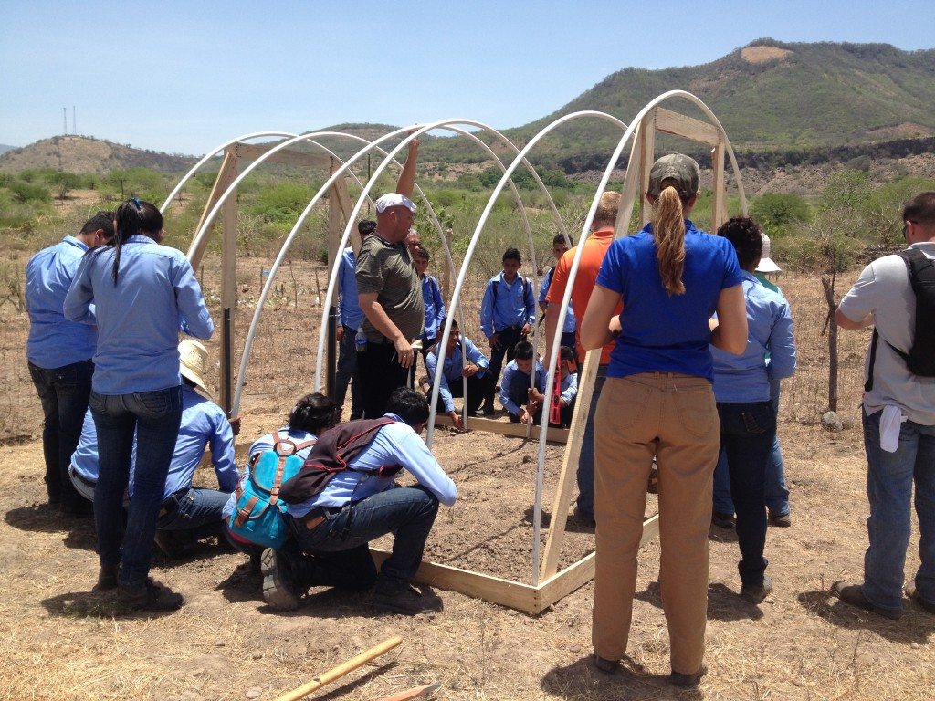 Students make a hoop house with an irrigation system.