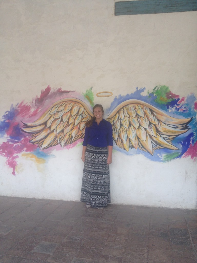 Emily poses with angel wings on one of the buildings in the city.