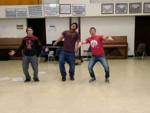 Image of three young men in a drama exercise.