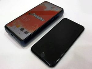 A very thick energizer phone sitting next to a thin iPhone