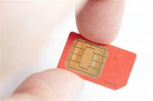 A SIM card being held between two fingers.