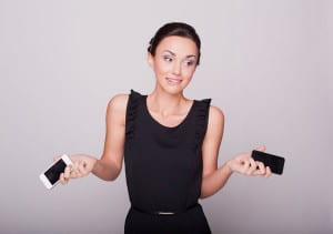 Woman holding two cellphones shrugging