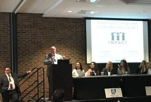 five female panelists sit at a table onstage in front of a screen with the IMPACT logo projected onto it. to their left a man speaks at a podium. to his left, Glenn Martinez stands on the stage stairs.