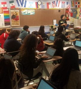 Carla Mello stands at the front right corner of a classroom. In front of her are several rows of desks where students are seated, and behind her is a wall with a cork board and banner of the flags of Latin America.