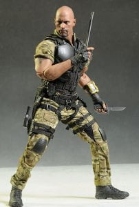GI Joe doll from the 2000s holding weapons. He has visibly large, bulging muscles in his upper and lower body.