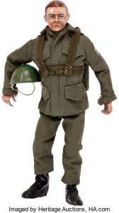 GI Joe doll from 1964 dressed in full body green fatigues, holding a helmet. He is of average/slim body size/shape