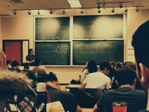 Photo taken from the back of a classroom; students are looking at a professor and a blackboard