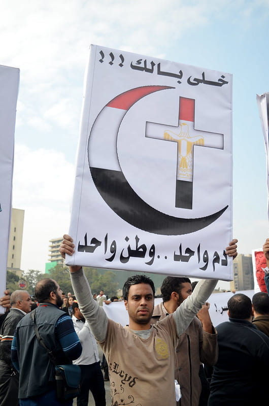image of protester with sign showing crescent and cross, Egypt