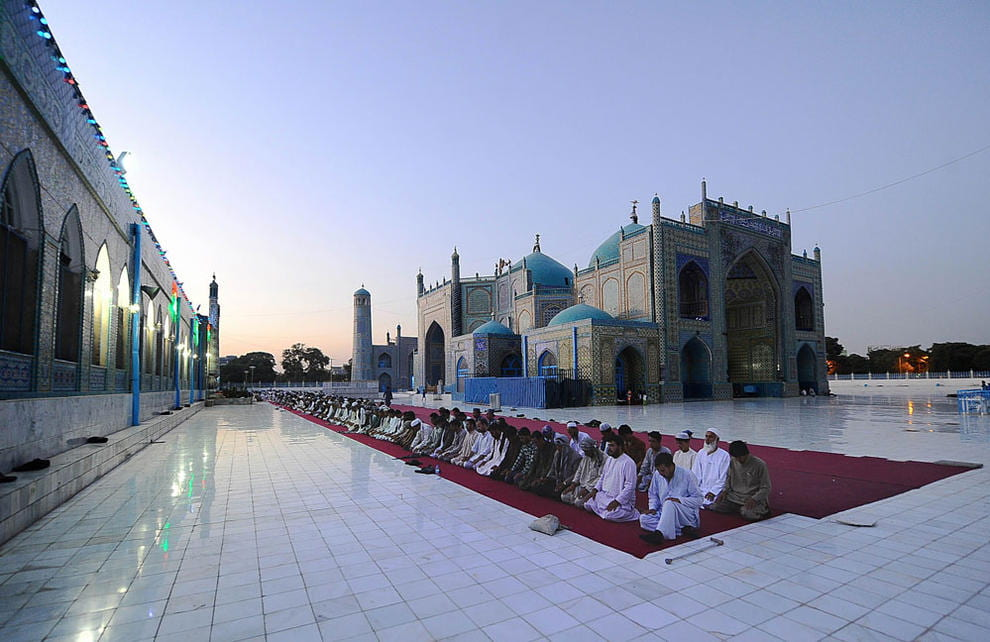 picture of men praying in front of a mosque in Afghanistan