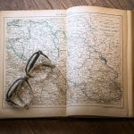 open atlas with folded glasses