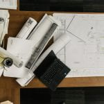 House plans, laptop, rolled drawings