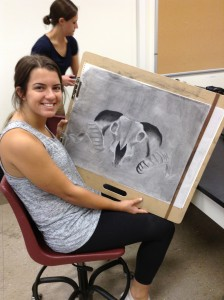 Student showing off her texture drawing of a skull