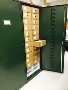 A herbarium case with two rows of boxes that contain packets of bryophyte specimens.