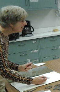 Donna Schenk cheerfully arranges some plant specimens