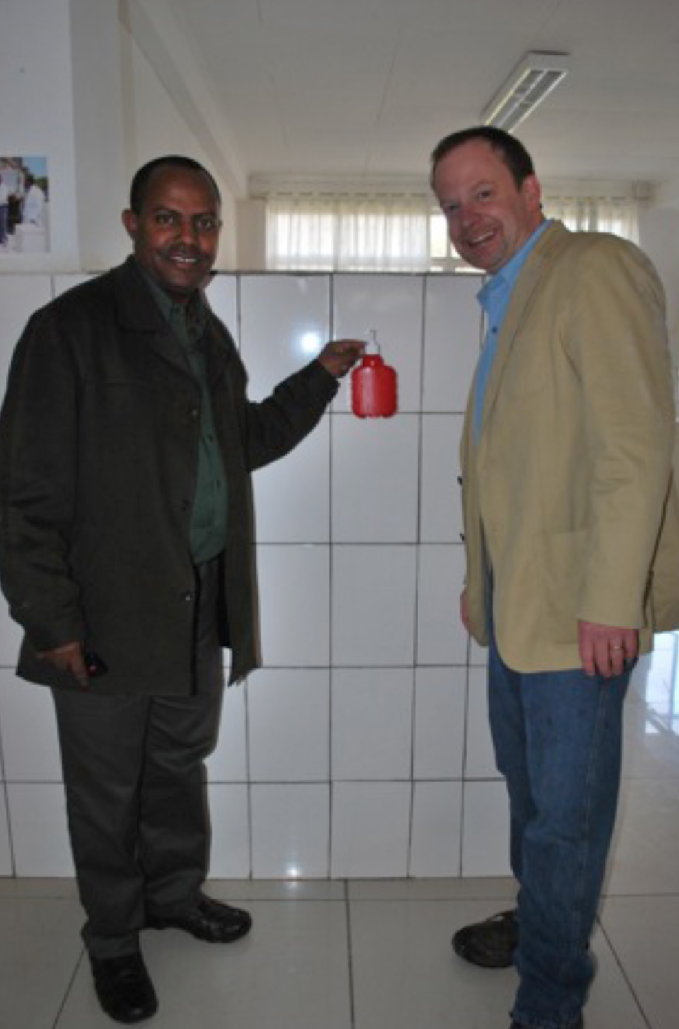 """Dr. Sisay Yifru, Dean of University of Gondar College of Medicine and Health Sciences demonstrates to me the use of a hand sanitizer dispenser on an inpatient unit at the University of Gondar Hospital.   These dispensers are manufactured at a local plastics factory.  The dispenser location and design demonstrate local adaptation of international """"best practices"""" for hand hygiene in health care facilities, including placing hand sanitizer at the """"point of care.""""  This technology was developed and deployed in cooperation with the Patient Safety Initiative, World Health Organization, but has been sustained by administrative support and leadership of the University of Gondar."""