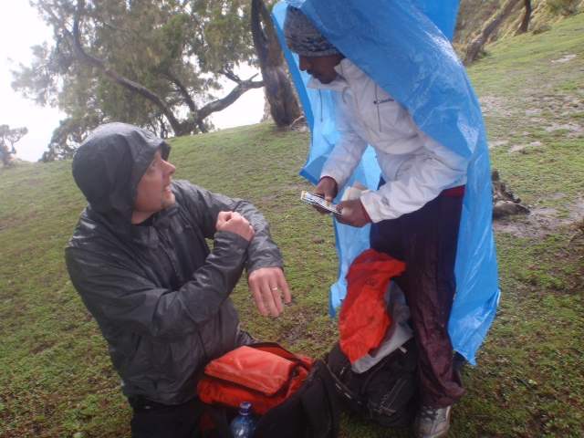 Simien Mountain tour guide Melese Beza of Outstanding Simien Mountains Tours and Tim Landers, RN, PhD do a show and tell of their first aid kits during a rain break while trekking through the Simien Mountains north of Gondar, Ethiopia.
