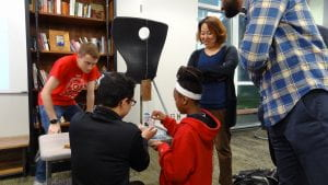 TEK8 student working with KIPP student watched by engineering faculty member