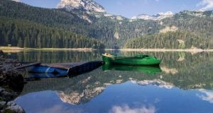 A bright green boat off of a dock in a lake that is reflecting the surrounding mountains and trees