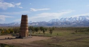 A tall tower in the middle of a flat valley with mountains in the background