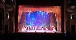 A brigtly light blue and red stage with dancers