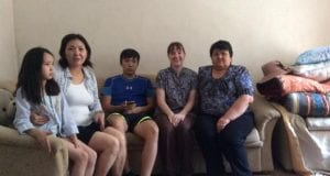 Five people sitting together on a couch