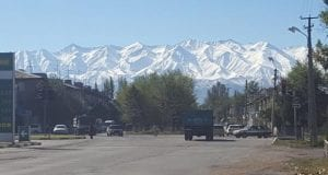 A wide city street with vehicles on it with snowcapped mountains in the background