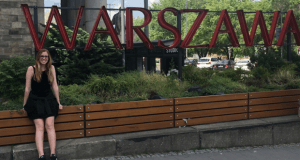 """Woman standing under a large red sign spelling """"Warszawa"""""""