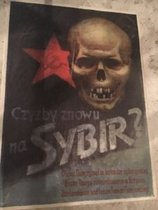 A poster with writing in Polish with a skull at the top and a red star with a hammer and sickle in it