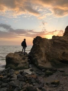 Man standing on a rock at the beach