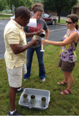 Teachers measure how much water has infiltrated through various types of soil in soup cans.