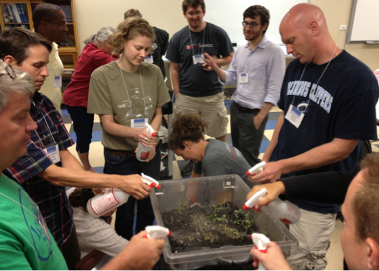 "Teachers at workshop measure simulate precipitation over a ""terrarium watershed"", and measure watershed outflow or runoff."