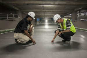 Construction supervisor and subordinate working in a parking garage