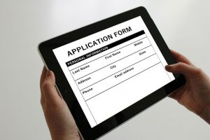 Man Filling Out an Online Job Application Form on Tablet