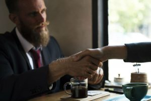 Man and woman shaking hands over coffee