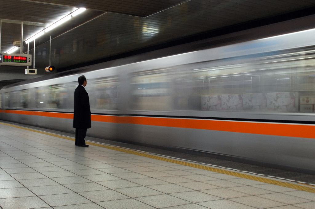 A man in a black trenchcoat stands alone on a subway platform with his back to the camera as a train with a bright orange stripe passes by.