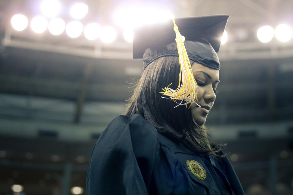 An African American woman walks across a stage in robe and graduation cap during a graduation ceremony.