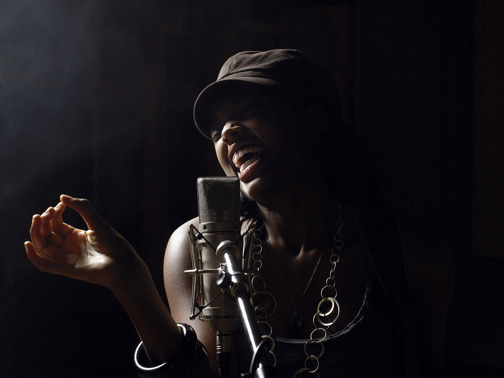 A young African American woman sings into a microphone, lit by a spotlight against a dark background