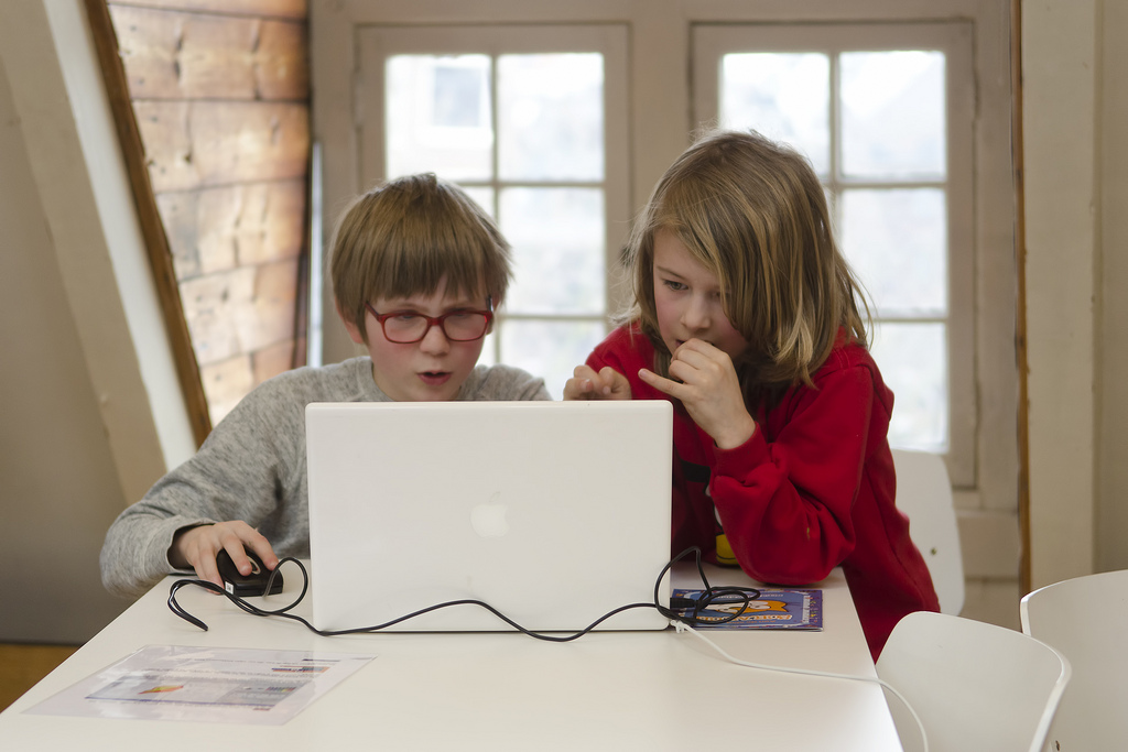 Two children sit at a table facing the camera and look at the screen of a laptop