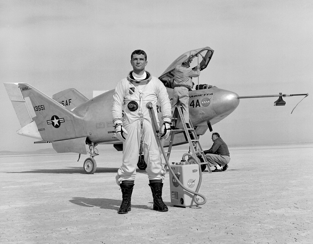 Pilot wearing flight suit and standing in from of a fighter jet. Black and white public domain photo from mid century United States.