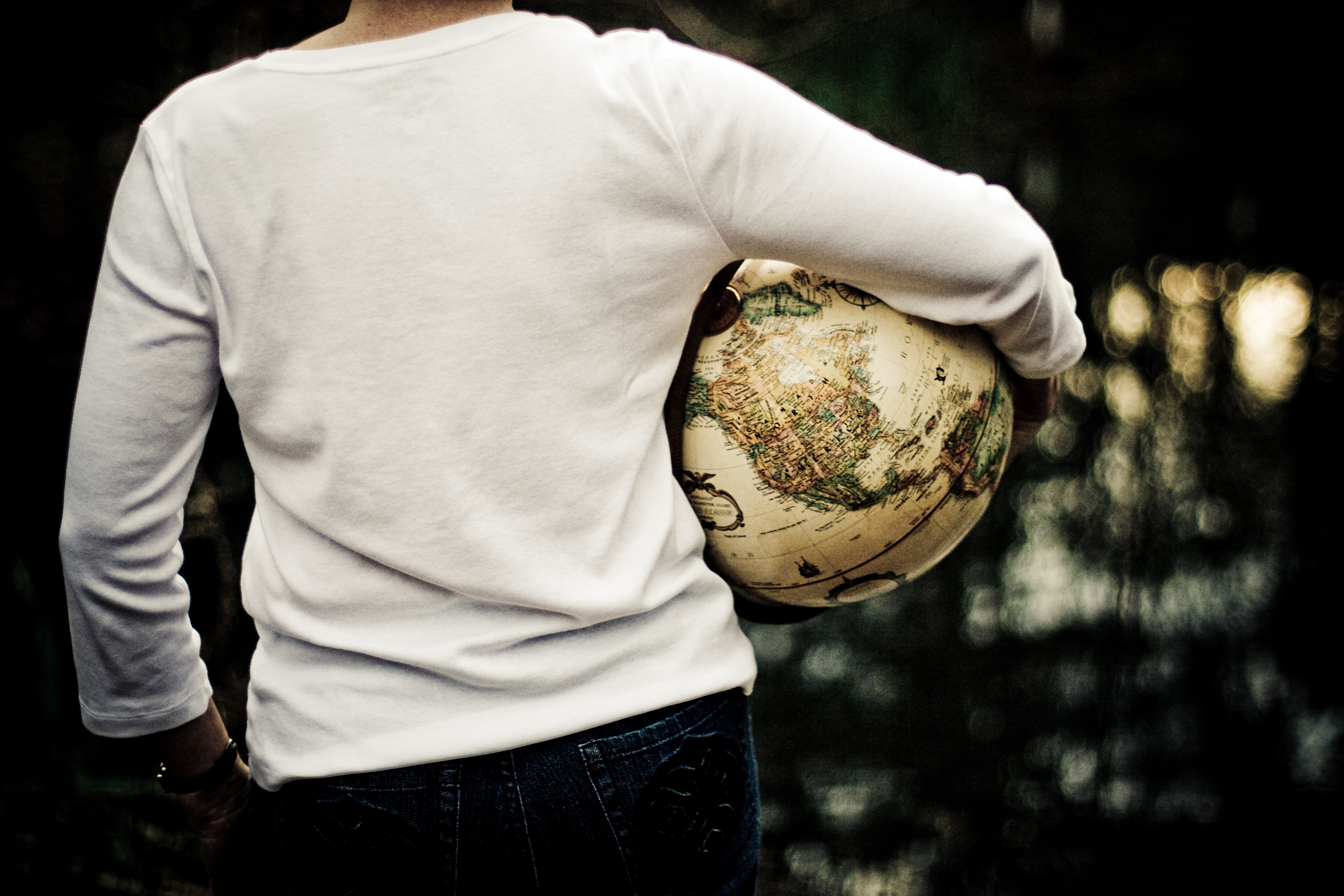 A woman from behind from the waist up, wearing blue jeans and a white shirt, holding an antique globe under one arm, and looking into the distance.