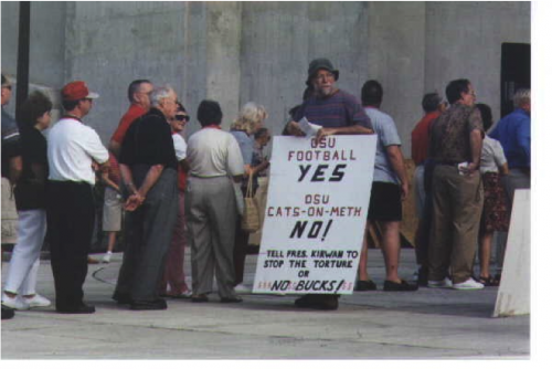 "A photograph from POET's website in 2005. Possibly from a protest Aug, 24th, 2001. (POET, 2005) The sign reads, ""OSU football / YES / OSU cats-on-meth / NO! / Tell pres. Kirwan to / stop the torture / or / NO BUCKS!"""