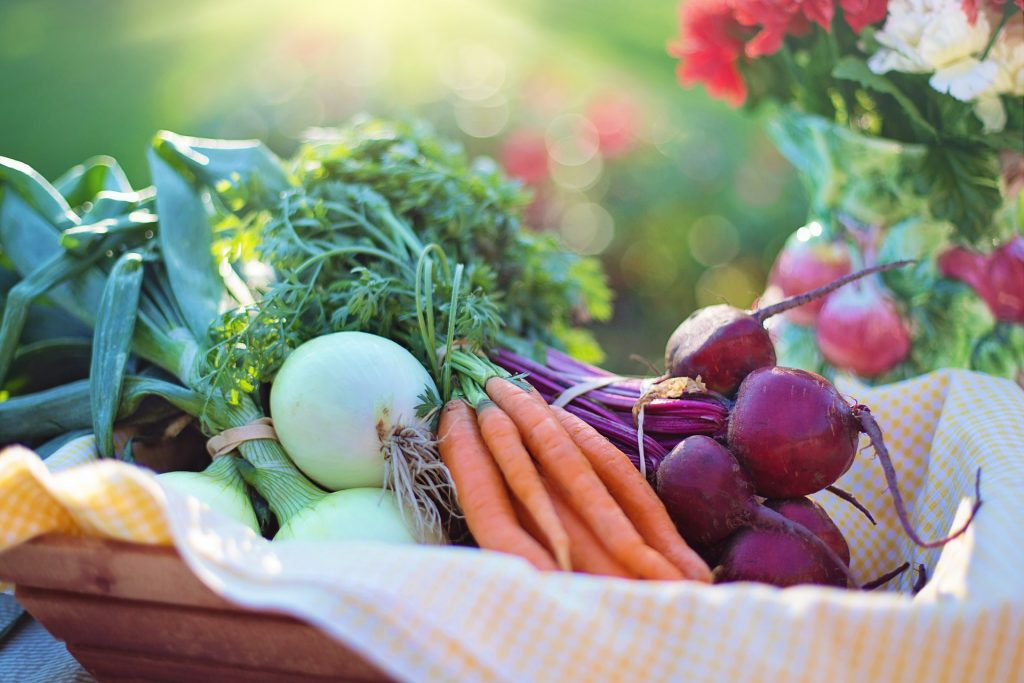 A basket of vegetables, including carrots, onions, and beets.