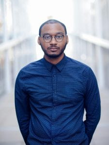 De'Avin stands in dark blue shirt buttoned to neck, arms behind his back. in front of blurry white grid