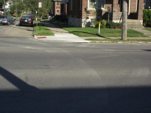 Street lacks crosswalks, creating dangerous conditions for pedestrians.