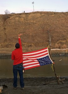 A water protector waves at police atop Turtle Mountain.