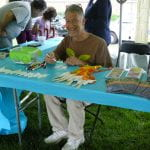 Educator at a craft activity table outdoors