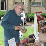Educator showing fossils at an outdoor booth